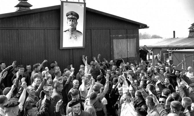Советские пленные подняли портрет Иосифа Сталина в честь освобождения Бухенвальда. Многие из них транзитом проследуют из Бухенвальда в ГУЛАГ.